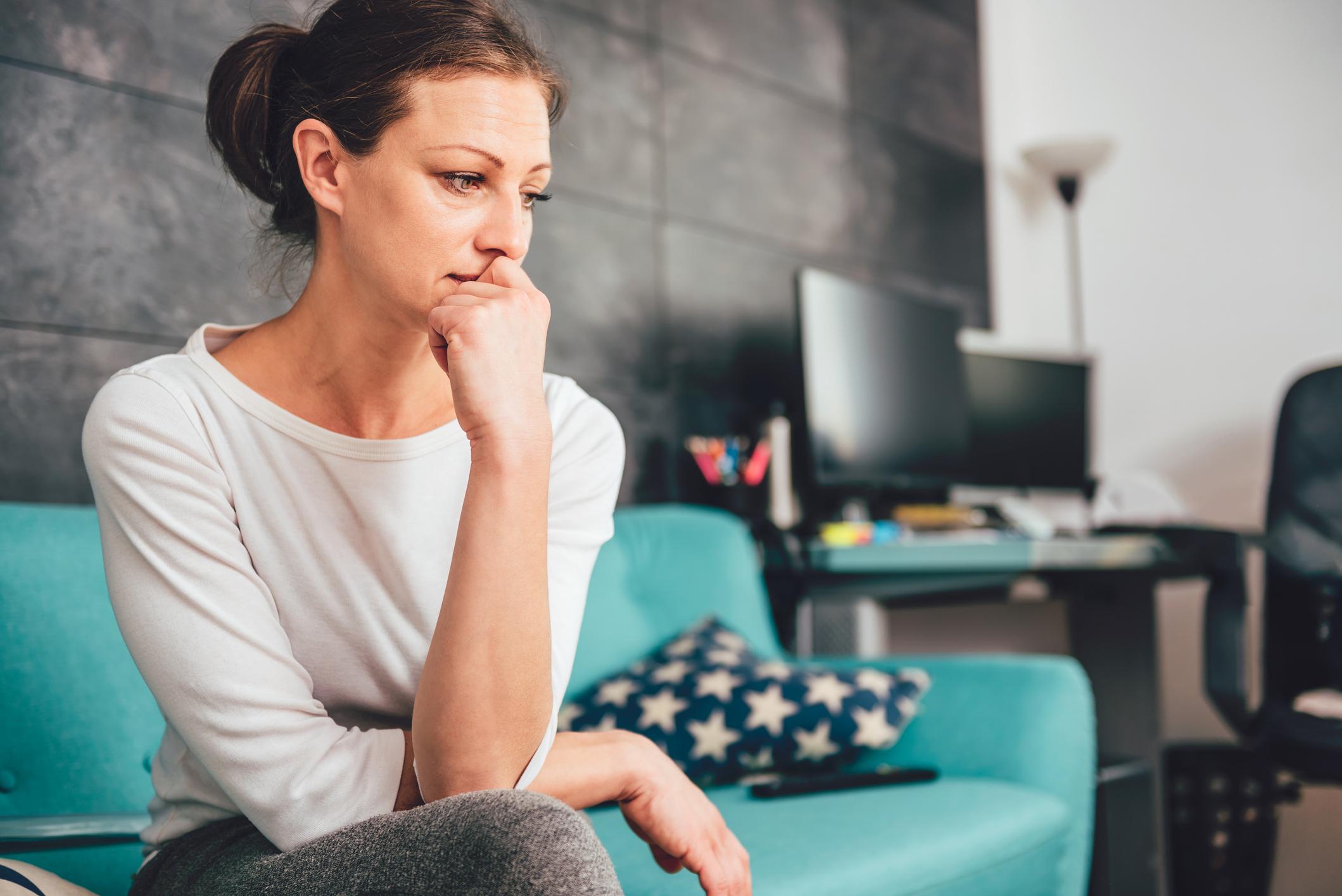 femme assise sur un canapé, seule, douteuse