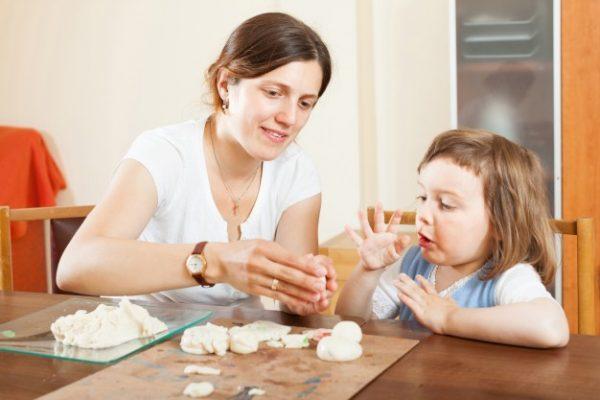 Une mère et sa fille font de la pâte à sel